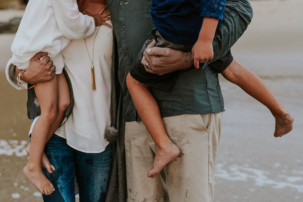 Orange County family photographer. Photo of daughter and son being held by mom and dad at the beach