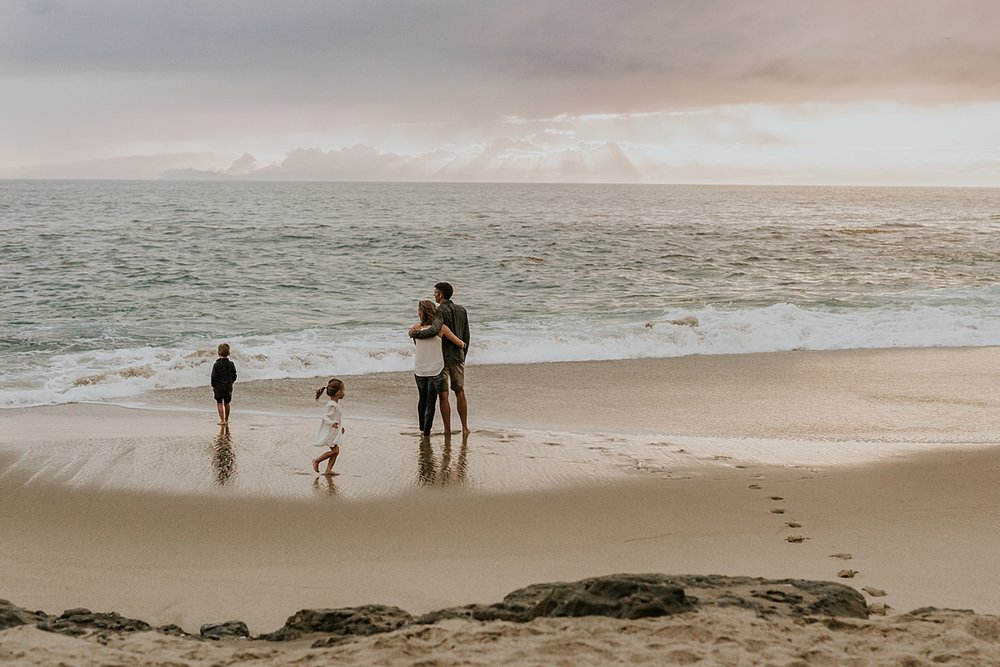 Orange County family photographer. family of four standing in front of the waves at Table Rock Beach Laguna Beach during photo session with Krystil McDowall Photography