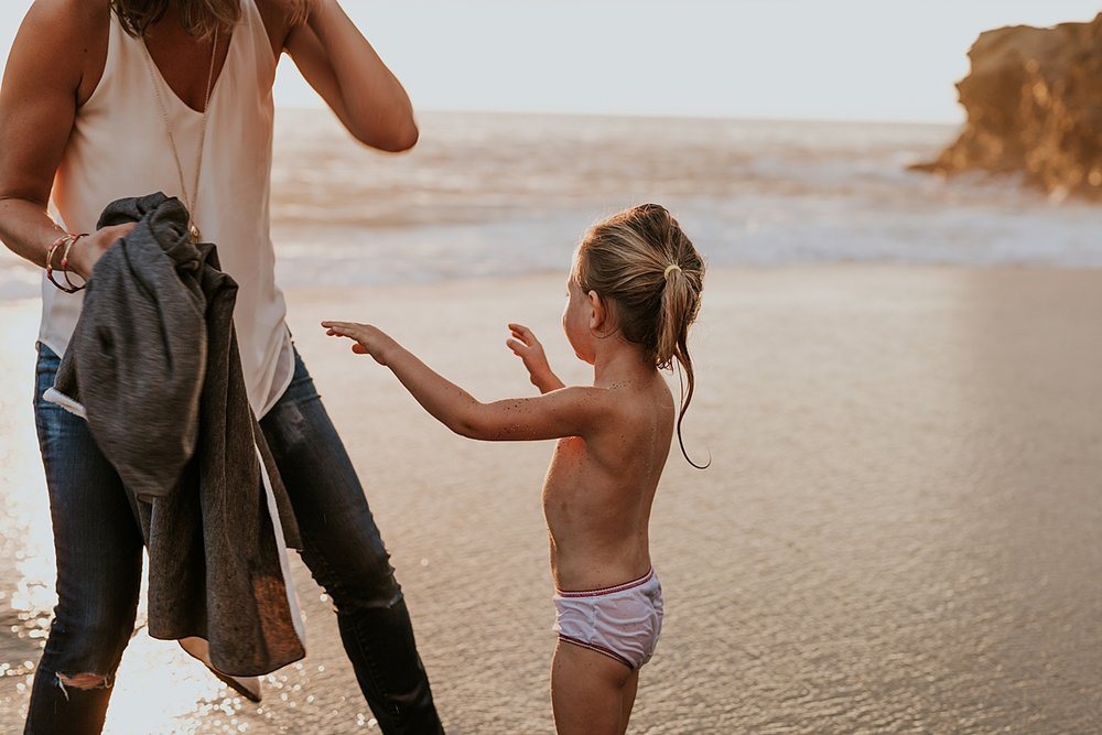 Orange County family photographer. Sweet daughter reaches out to her mom after she falls into the ocean at Table Rock Beach Laguna Beach during photo session with Krystil McDowall Photography
