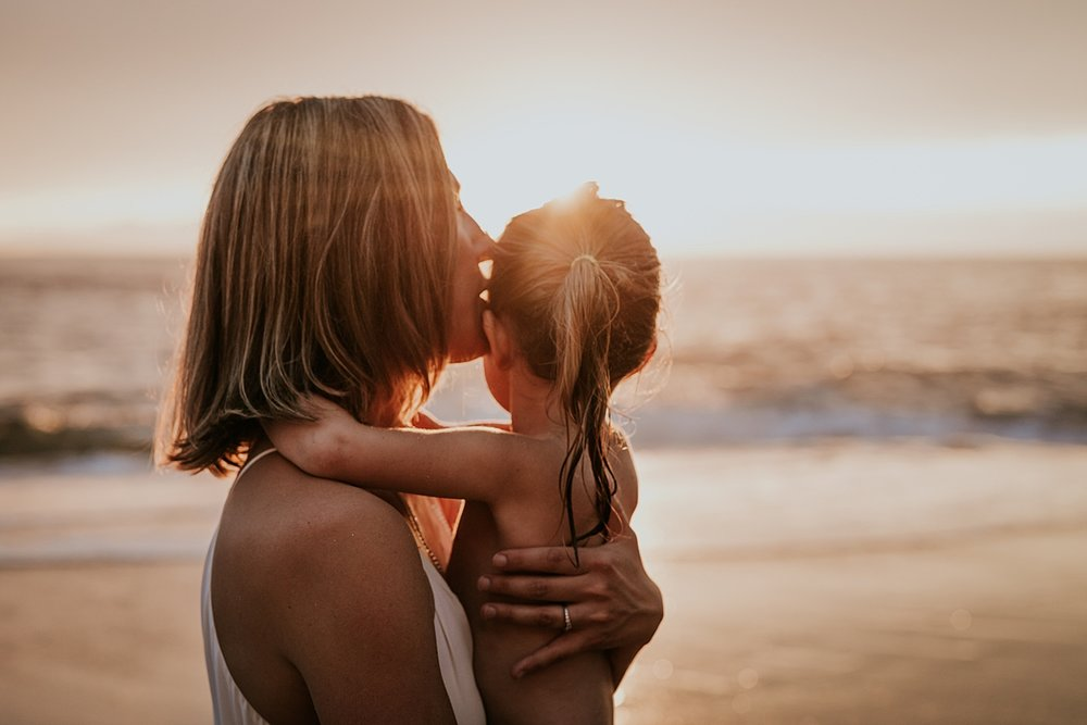 Orange County family photographer. Backlit photo of mom kissing daughter's face at sunset at Table Rock Beach Laguna Beach during photo session with Krystil McDowall Photography