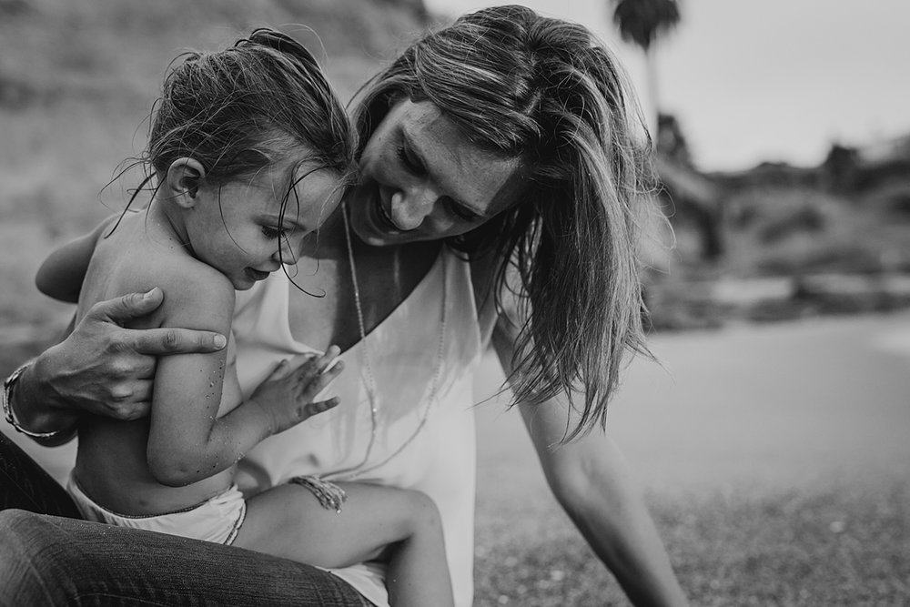 Orange County family photographer. Photo of mom and daughter sitting in the sand at Table Rock Beach Laguna Beach during photo session with Krystil McDowall Photography