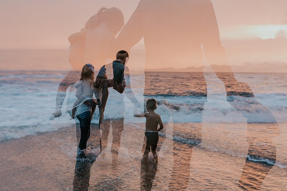 Orange County family photographer. Double exposure photo of family of four standing in ocean waves at sunset at Table Rock Beach Laguna Beach during photo session with Krystil McDowall Photography