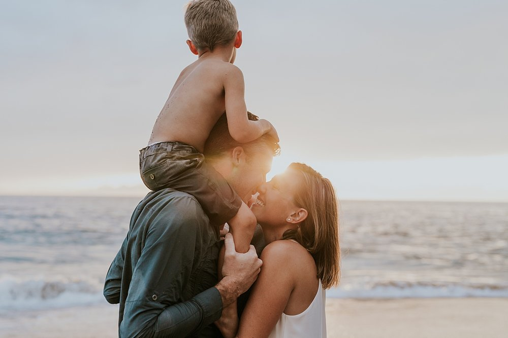Orange County family photographer. Photo of family of four cuddling in the ocean waves as the sunsets at Table Rock Beach Laguna Beach during photo session with Krystil McDowall Photography