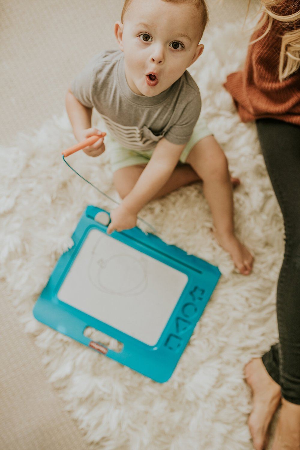 Orange County family photographer. Photo of toddler as he looks up surprised at the camera during in-home newborn session with Krystil McDowall Photography