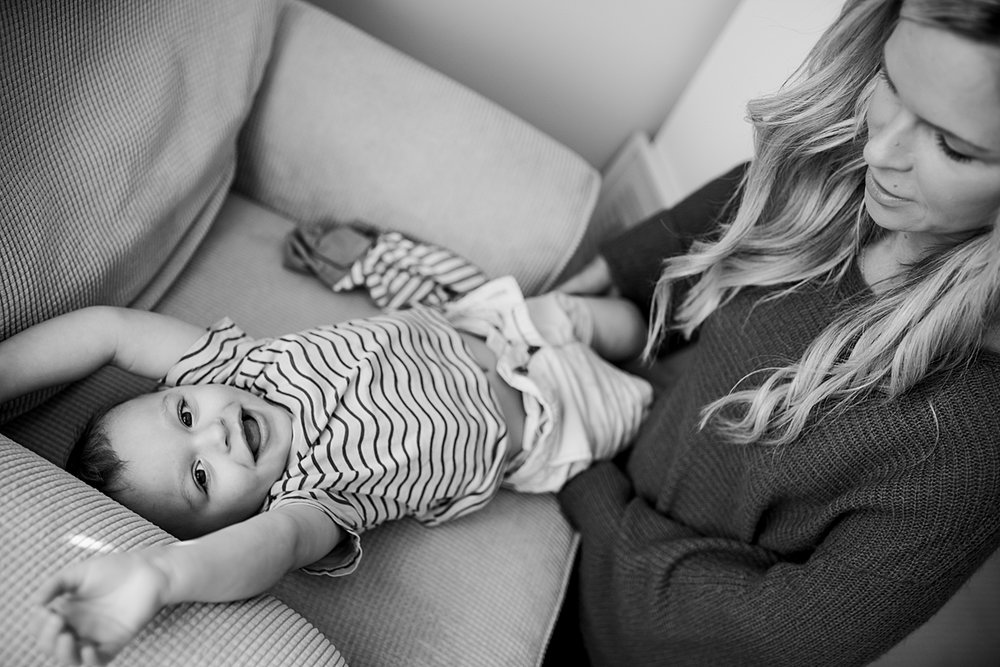 Orange County family photographer. photo of mom changing clothes of her toddler during in-home newborn session with Krystil McDowall Photography