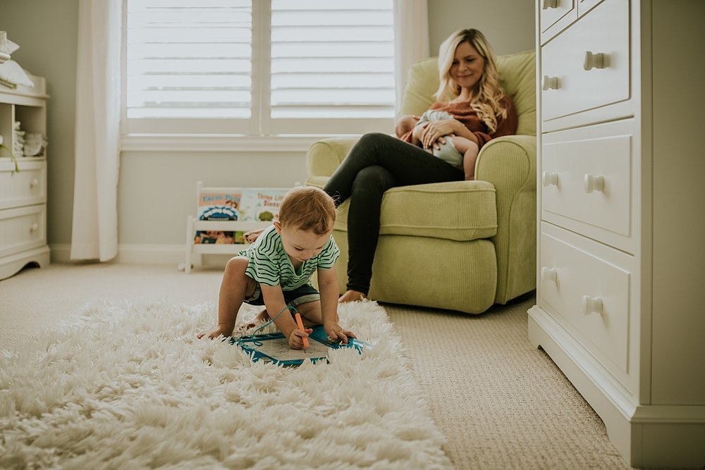 Orange County family photographer. Candid photo of mom rocking her newborn son while her toddler son plays with toys in front of her