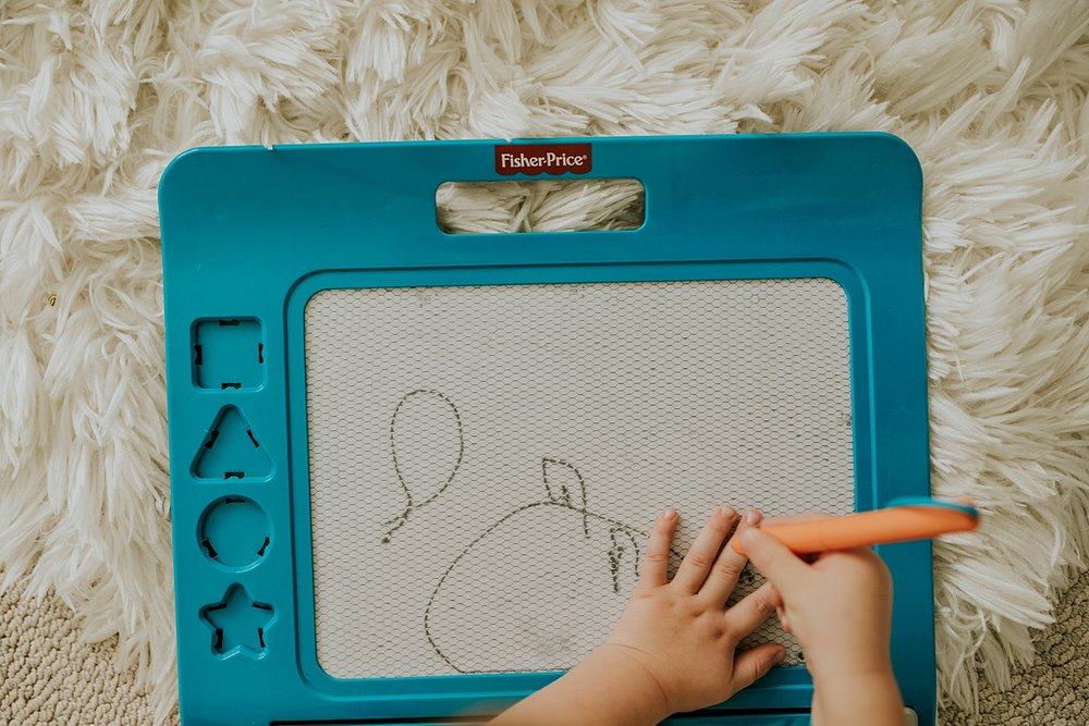 Orange County family photographer. Close up photo of boy tracing his hand with his doodle pro in his room