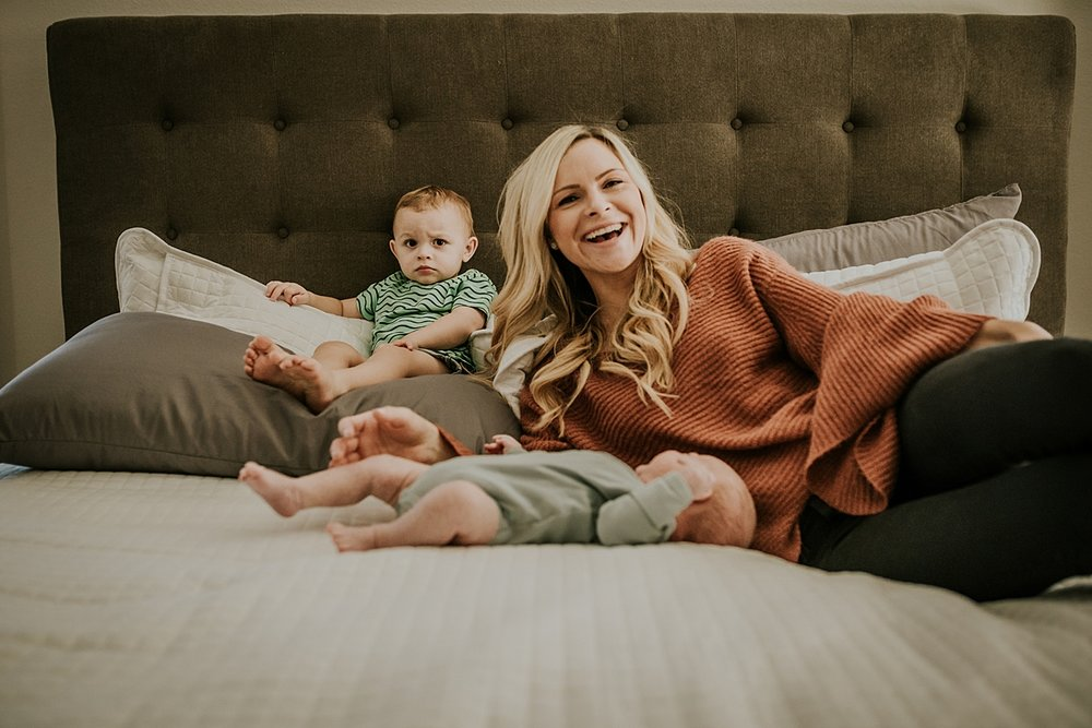 Orange County family photographer. Candid photo of mom and her toddler and newborn son all laying on mom's bed during in home newborn session