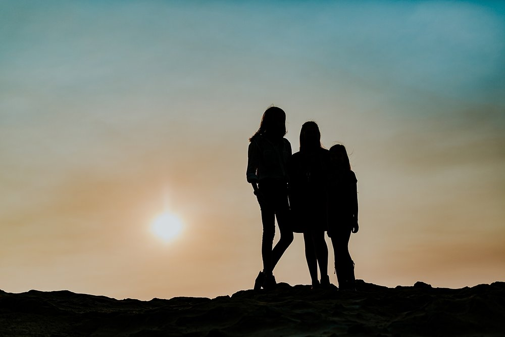Orange County family photographer. Silhouette image of mom and her two daughters standing at sunset during family photo session at Top of the World Laguna Beach