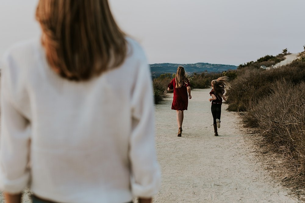 Orange County family photographer. Candid image of mom looking over daughters as they run in the distance on the dirt road at Top of the World Laguna Beach