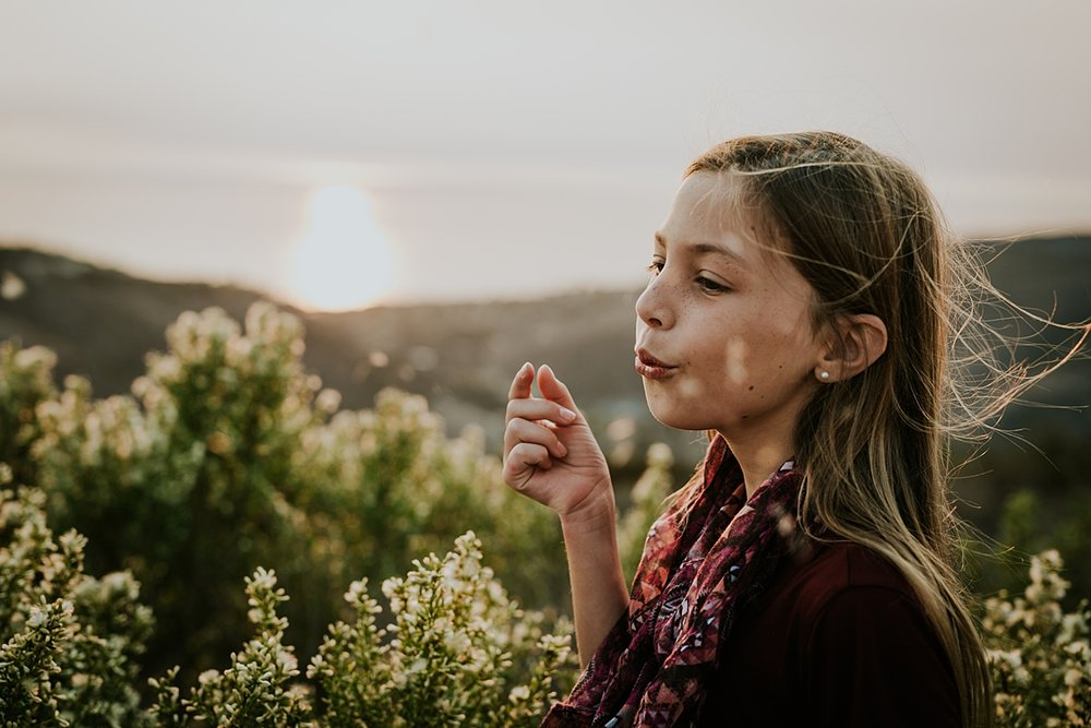 Orange County family photographer. Photo of daughter blowing flowers into the sky at sunset at Top of the World Laguna Beach