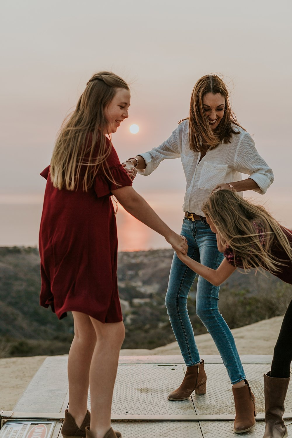 Orange County family photographer. Photo of mom and daughters holding hands as the sunsets during candid family photo session at Top of the World Laguna Beach