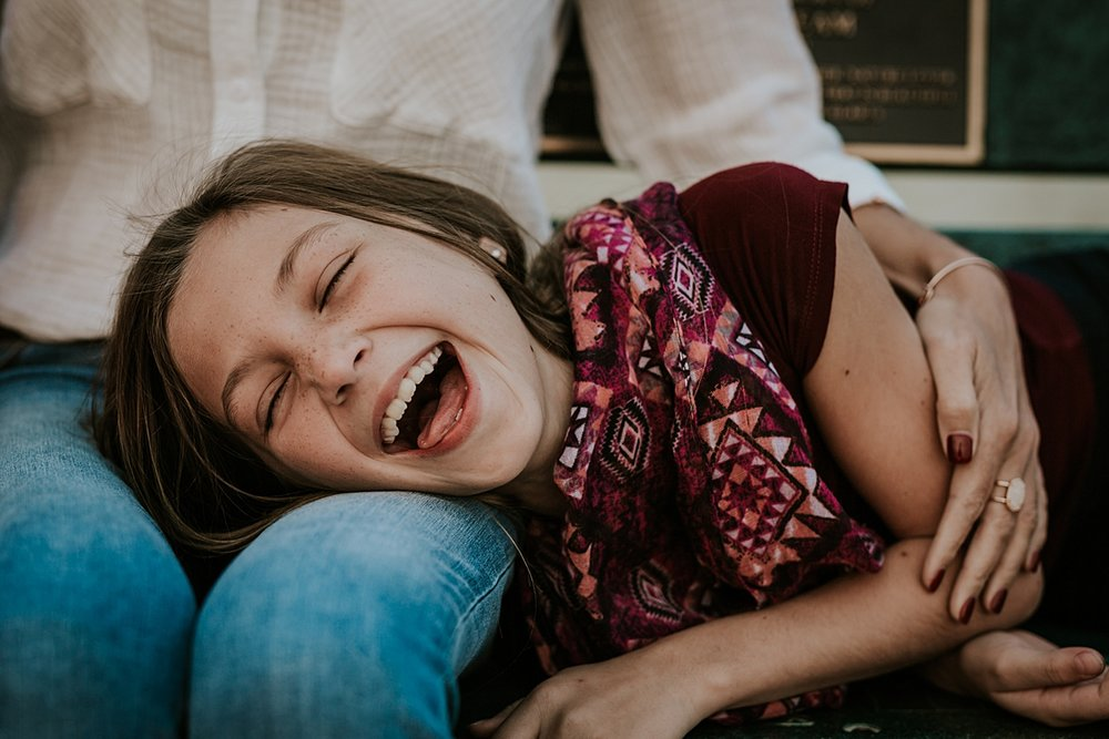 Orange County family photographer. Candid photo of young girl laughing hard as she lays on her mom's lap during family photo session at Top of the World Laguna Beach