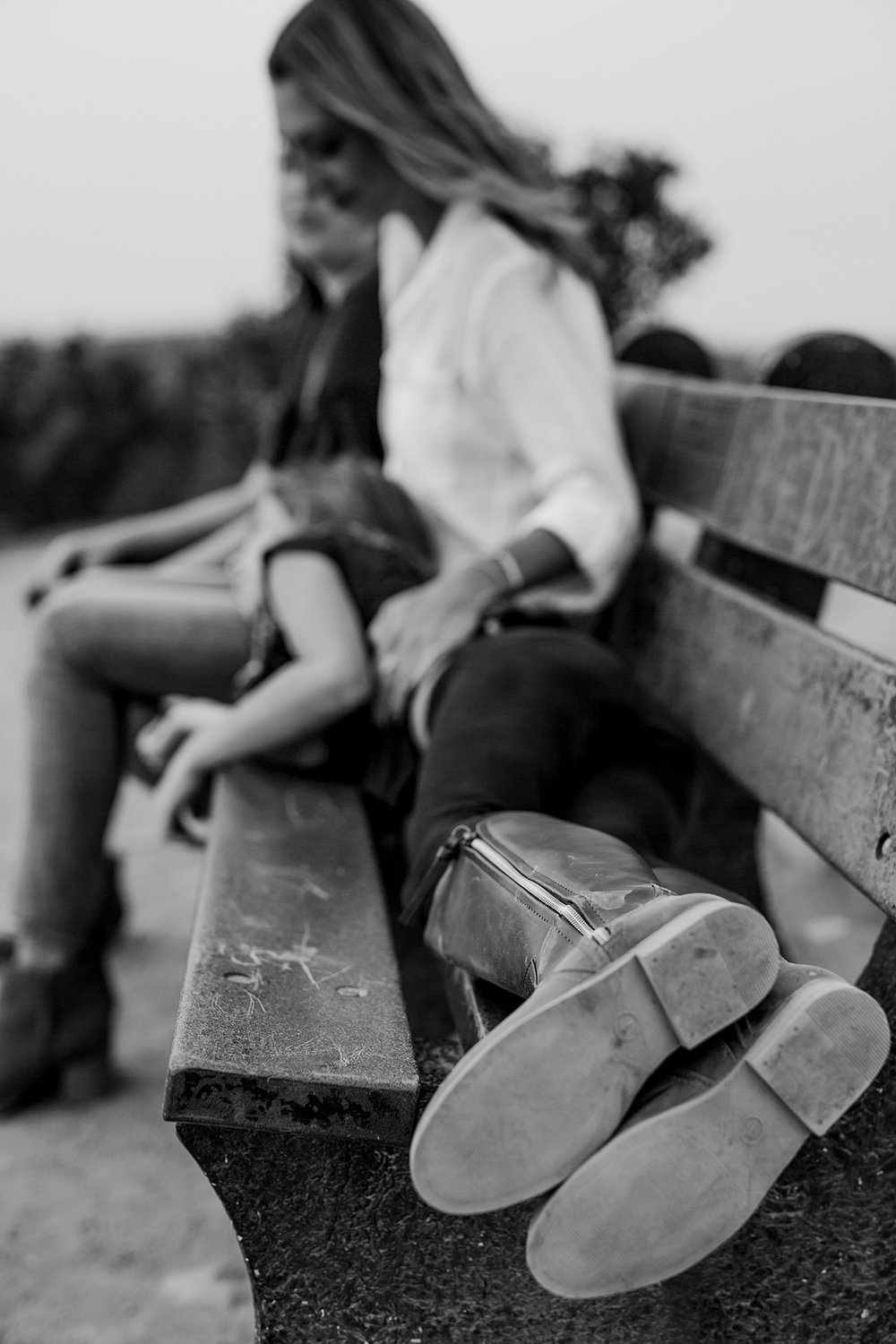 Orange County family photographer. Photo of daughter's boots taken as she lays strewn across her mom sitting on park bench at Top of the World Laguna Beach