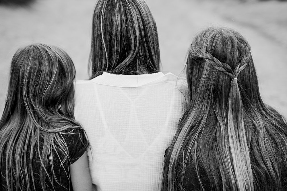 Orange County family photographer. Portrait of mom and her daughters taken from behind showing their long locks of beautiful hair taken by Krystil McDowall Photography