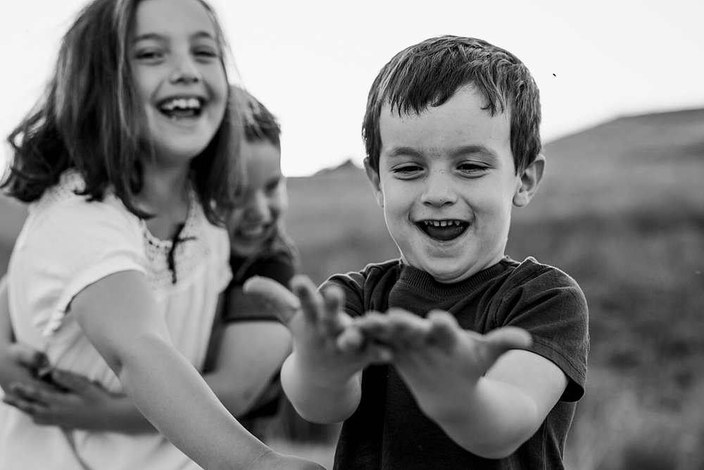 Orange County family photographer. Candid photo of brothers and sister laughing and mucking around at family photo shoot at Quail Hill by Krystil McDowall