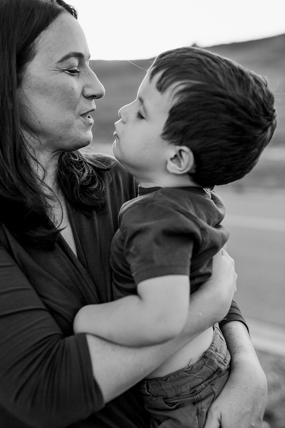 Orange County family photographer. Black and white portrait of mom and her youngest son looking into each others eyes sweetly while embracing each other during family photo shoot at Quail Hill