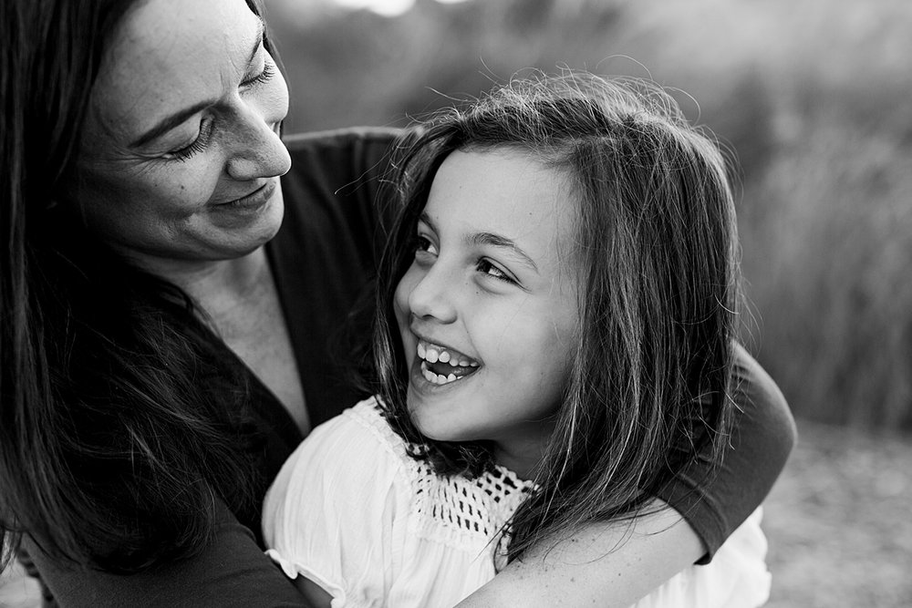Orange County family photographer. Beautiful black and white portrait of mom and her daughter looking lovingly into each other's eyes during family photo shoot at Quail Hill