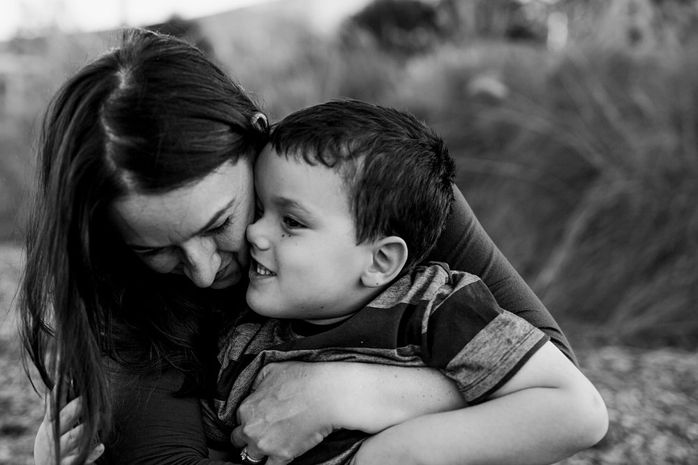 Orange County family photographer. Beautiful candid black and white photo of boy pressing his nose up against his mom's cheek during family photo shoot at Quail Hill