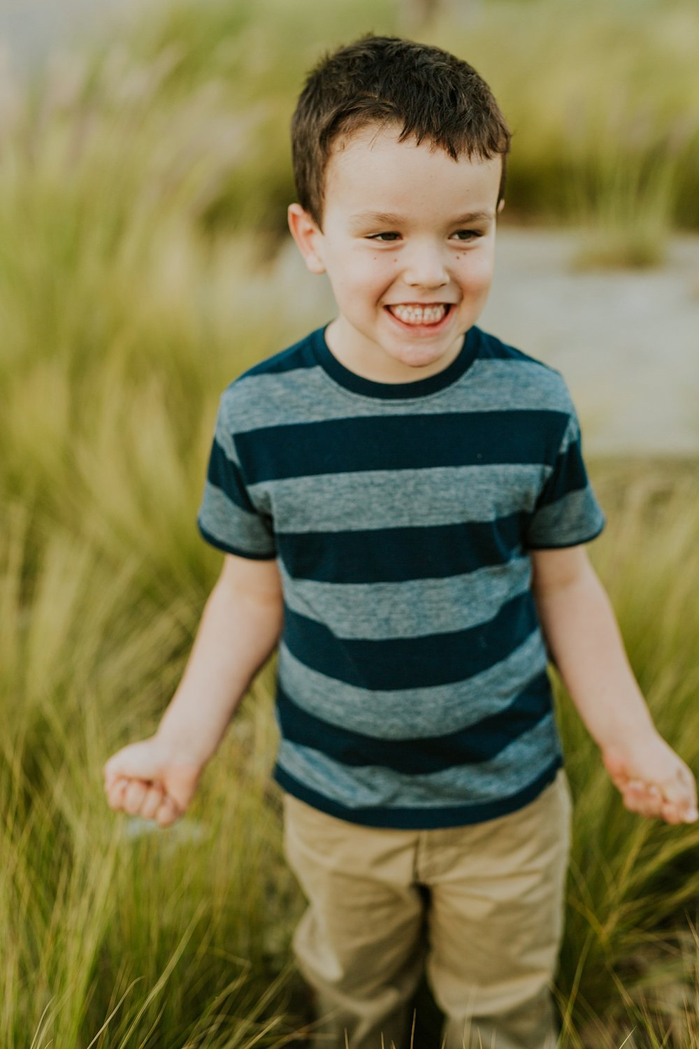 Orange County family photographer. Portrait of young boy standing in tall green grass during family photo shoot at Quail Hill with Krystil McDowall Photography