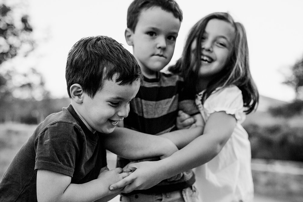Orange County family photographer. Candid photo of three siblings laughing as they play games with each other during family photo shoot at Quail Hill with Krystil McDowall Photography