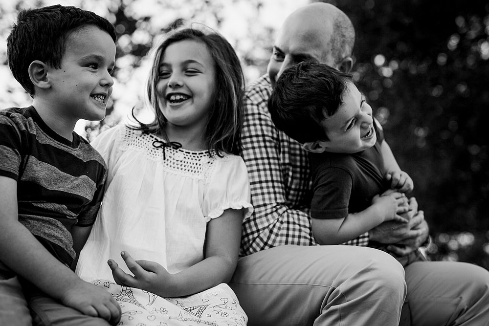 Orange County family photographer. Candid photo of dad and his 3 kids sitting on stone wall and playing together during family photo shoot at Quail Hill with Krystil McDowall Photography