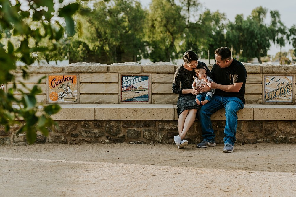 Orange County family photographer. Family portrait of family sitting on bench that was an orange picking lot during outdoor family photo session at Jeffrey Open Space Trail Irvine