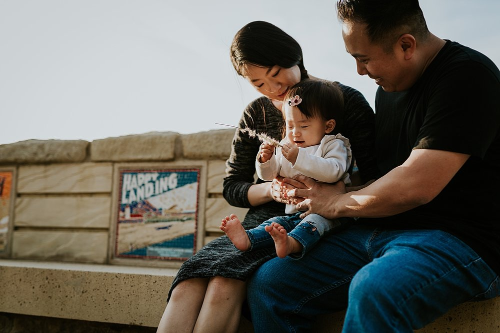 Orange County family photographer. Portrait of mom, dad and daughter sitting on tiled bench while girl plays with dandelion during outdoor family photo session at Jeffrey Open Space Trail Irvine