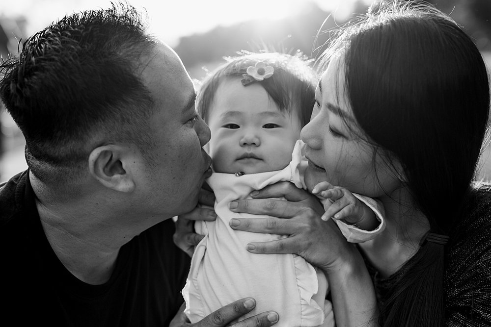 Orange County family photographer. Black and white portrait of mom, dad and daughter snuggling with sunset in the background during family photo shoot at Jeffrey Open Space Trail Irvine