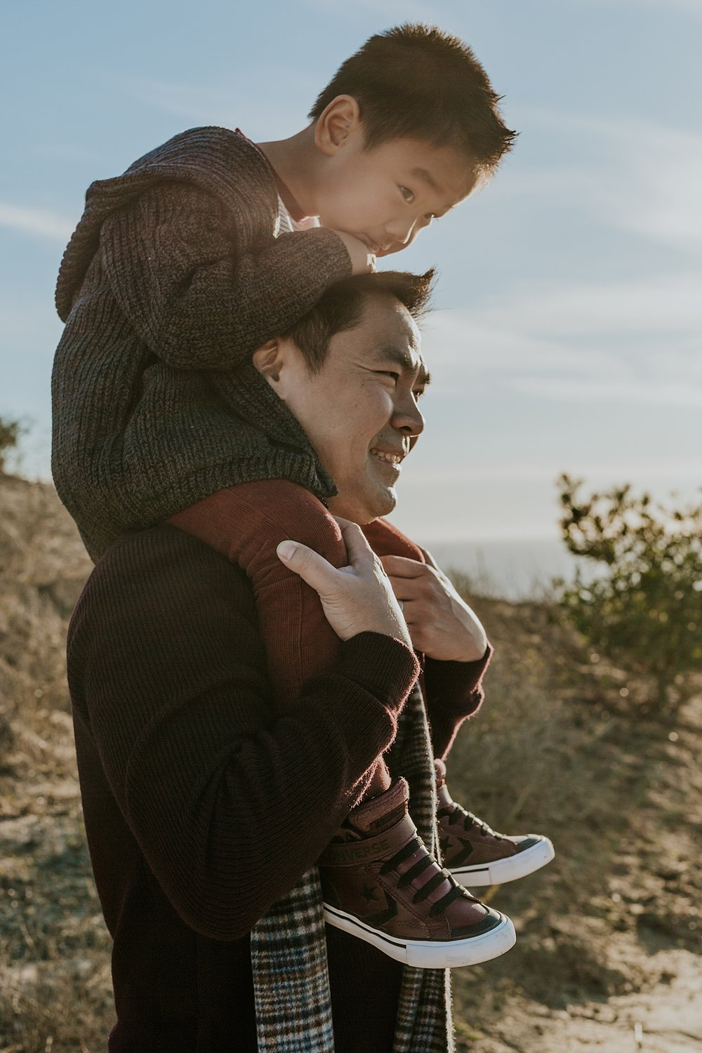 Orange County family photographer. Dad gives his son a shoulder ride while son rests on dad's head at Top of the World Laguna Beach during outdoor family photo session