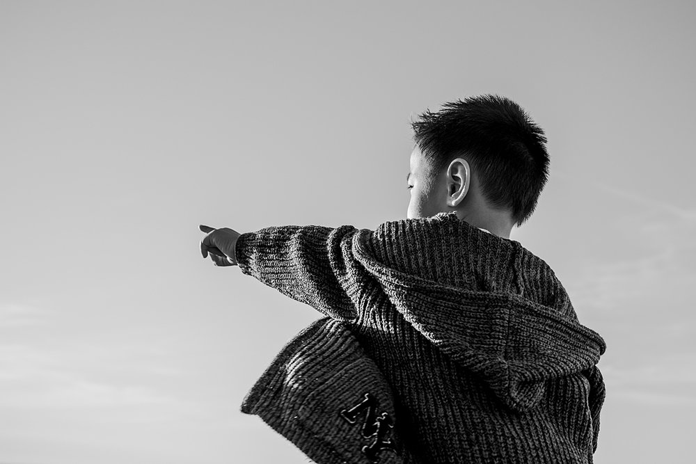 Orange County family photographer. Candid black and white photo of boy pointing to the horizon during during outdoor during family photo session at Top of the World Laguna Beach