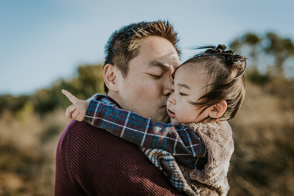 Orange County family photographer. Photo of dad giving his daughter a kiss as she points to the mountains during during outdoor during family photo session at Top of the World Laguna Beach