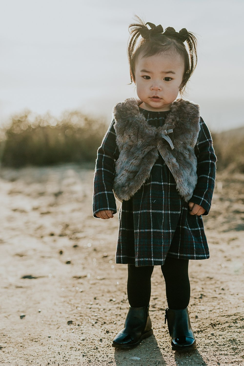 Orange County family photographer. Portrait of young toddler in her beautiful black boots standing on dirt road during outdoor during family photo session at Top of the World Laguna Beach