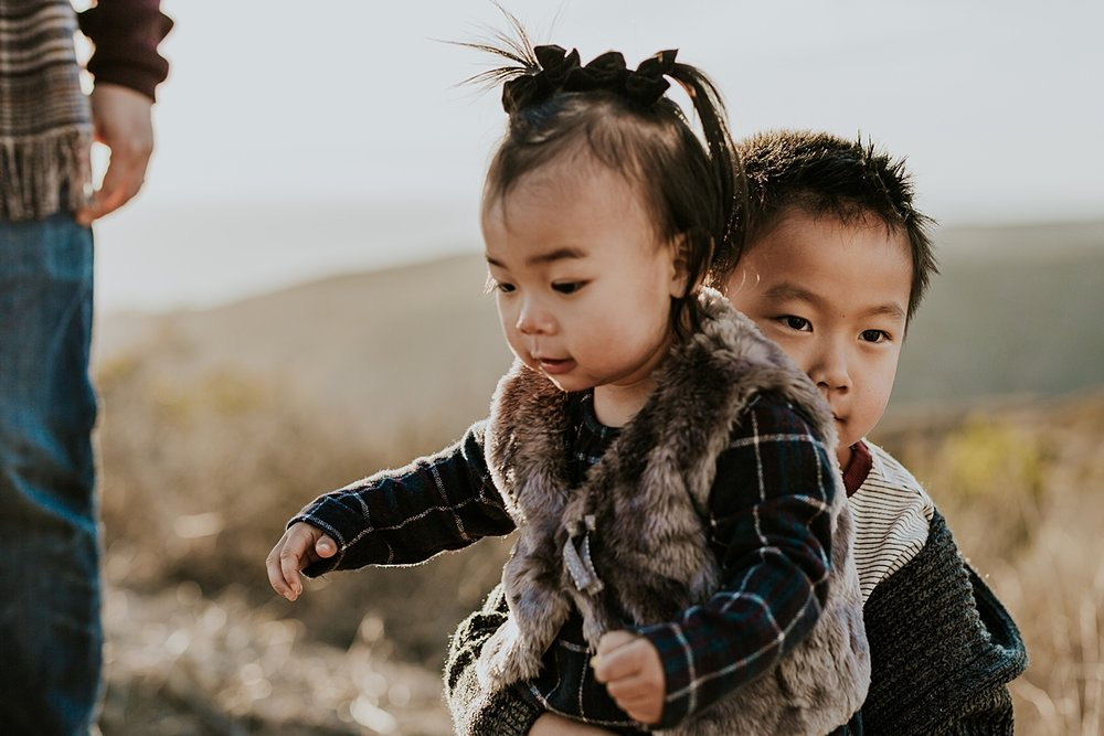 Orange County family photographer. Candid photo of older brother giving younger sister a sweet hug with sunset in the background during outdoor during family photo session at Top of the World