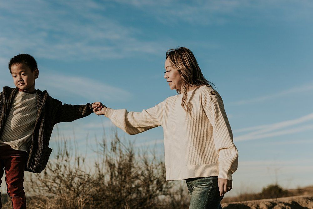 Orange County family photographer. Candid photo of mom walking hand in hand with her son during outdoor during family photo shoot at Top of the World Laguna Beach