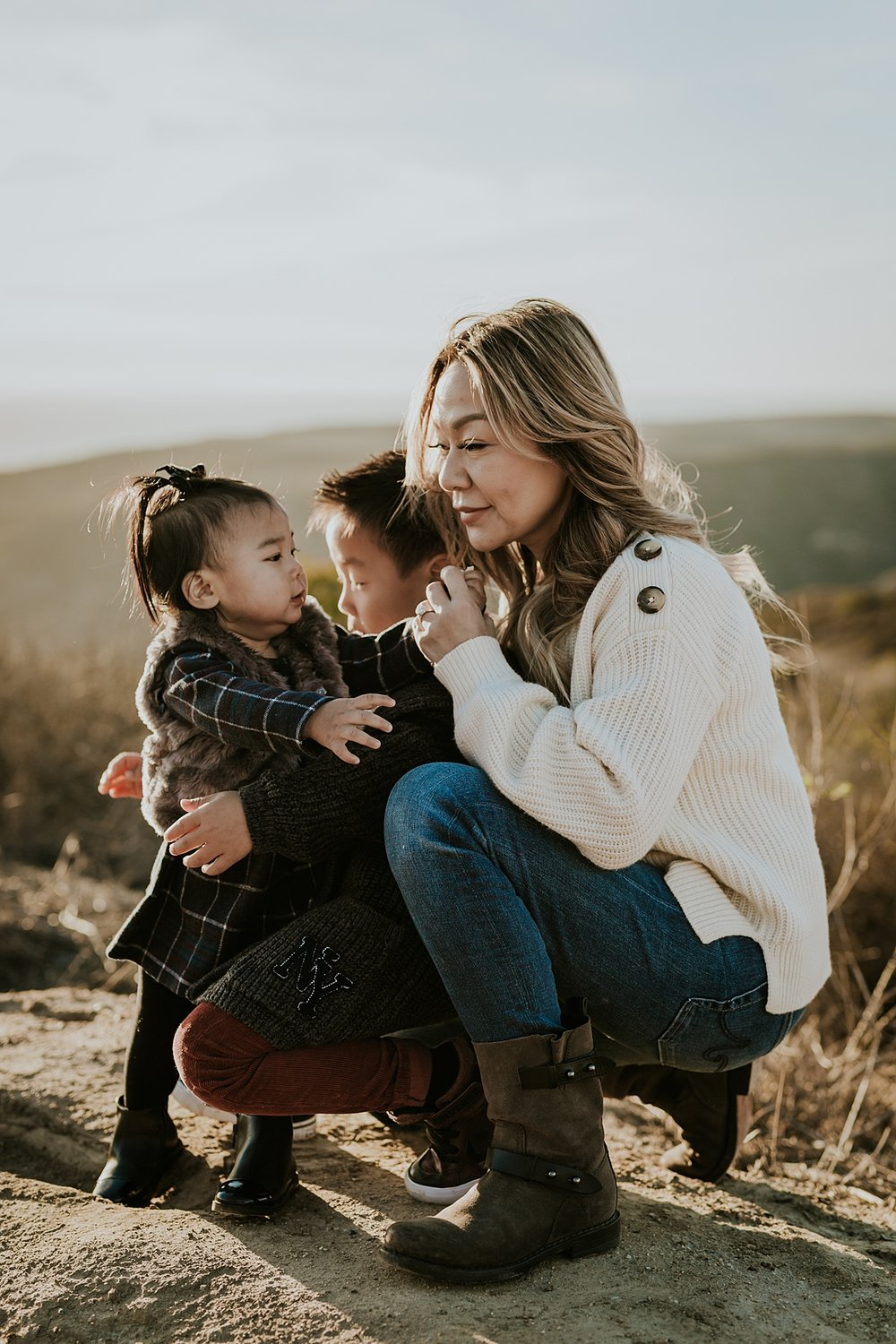 Orange County family photographer. Portrait of mama and her two babes hugging and playing on the dirt road during outdoor during family photo session at Top of the World Laguna Beach