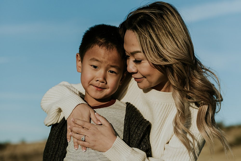 Orange County family photographer. Portrait of mom and her son with mom's arms wrapped around her boy and bright blue sky in the background. photo by Krystil McDowall Photography