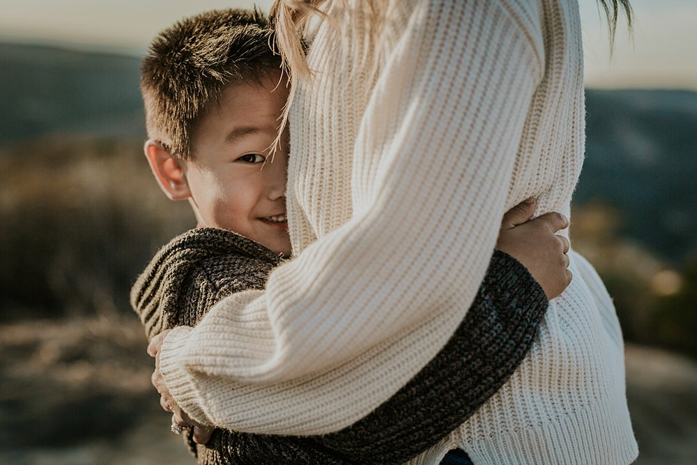 Orange County family photographer. Candid photo of young boy smiling as he squeezes his mom for a big hug during outdoor during family photo shoot at Top of the World Laguna Beach