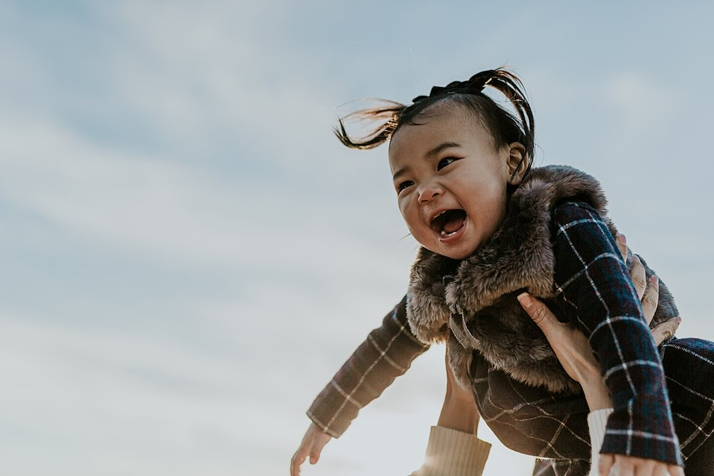 Orange County family photographer. Photo of sweet girl in pigtails being thrown in the air during outdoor during family photo shoot at Top of the World Laguna Beach CA