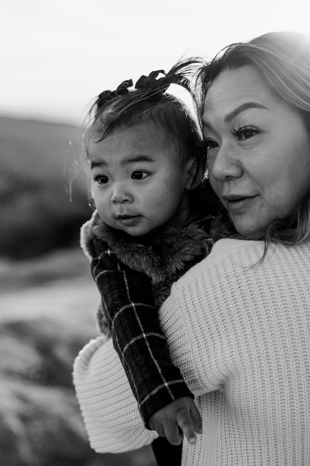 Orange County family photographer. Portrait of mom and daughter looking into the distance during outdoor during family photo shoot at Top of the World Laguna Beach CA
