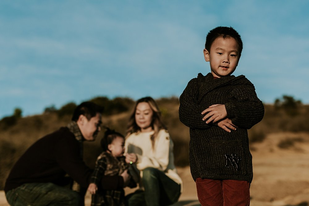 Orange County family photographer. Photo of young boy arms crossed with his mom, dad and sister playing in the background during outdoor during family photo shoot at Top of the World Laguna Beach CA