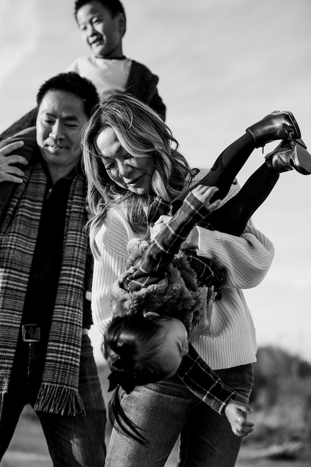 Orange County family photographer. Photo of mom tipping daughter upside down and dad giving son a shoulder ride during outdoor during family photo shoot at Top of the World Laguna Beach CA
