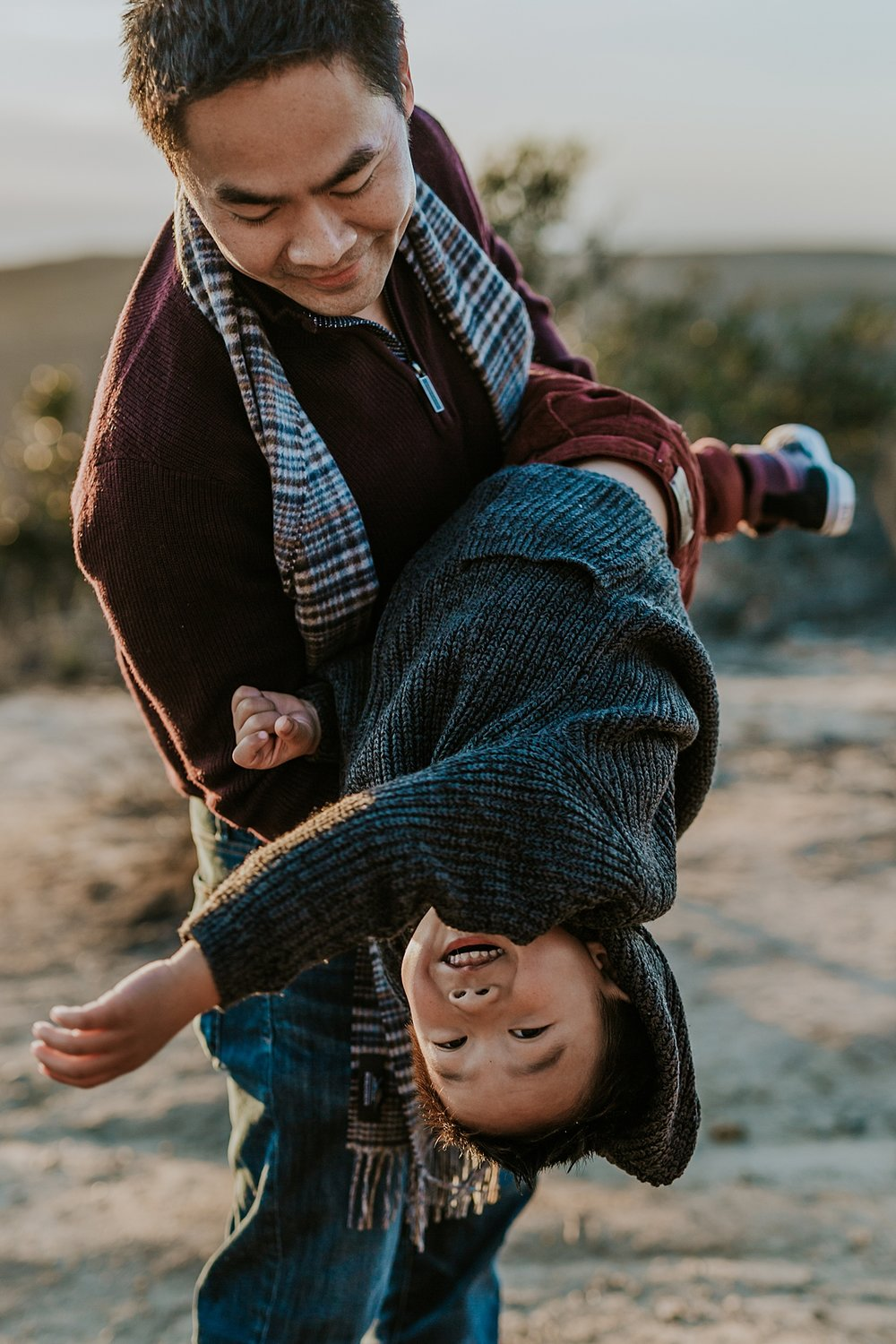 Orange County family photographer. Candid photo of dad swinging his son around during outdoor during family photo shoot at Top of the World Laguna Beach CA