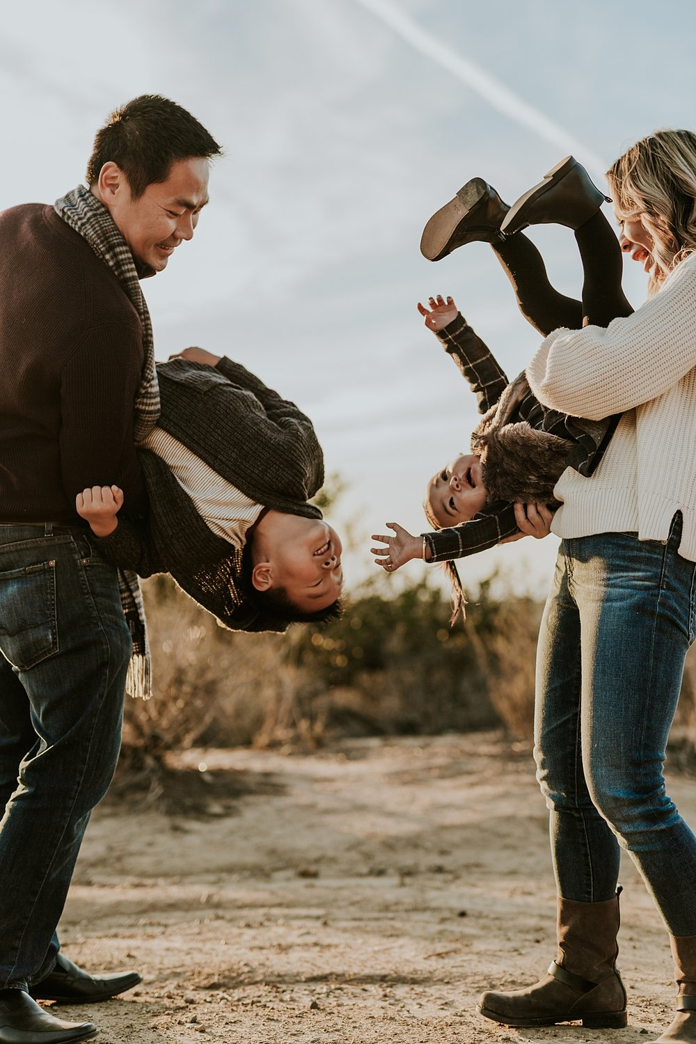Orange County family photographer. Photo of mom tipping daughter upside down and dad tipping son upside down during outdoor during family photo shoot at Top of the World Laguna Beach CA