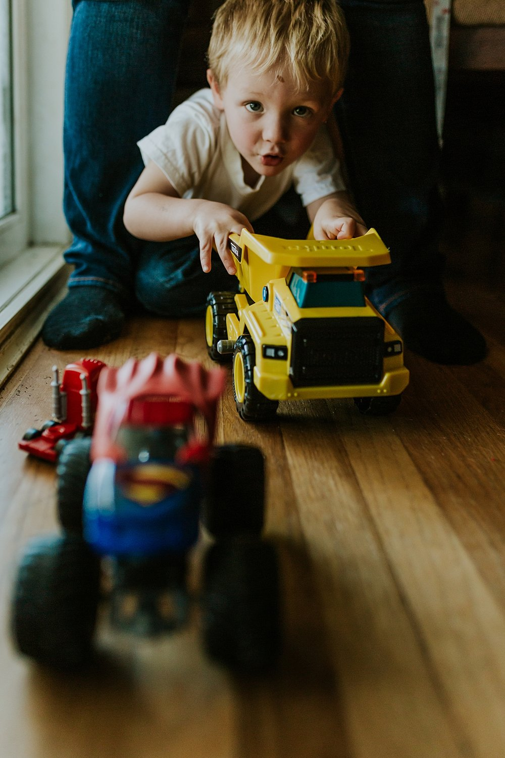 Orange County family photographer. Big brother plays with trucks during in home newborn session with Krystil McDowall Photography