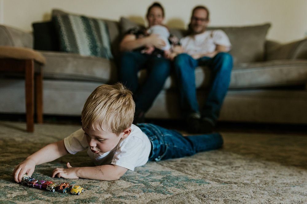 Orange County family photographer. Candid photo of toddler playing with cars on the carpet while mom, dad and newborn son hang out in the background during in home newborn session