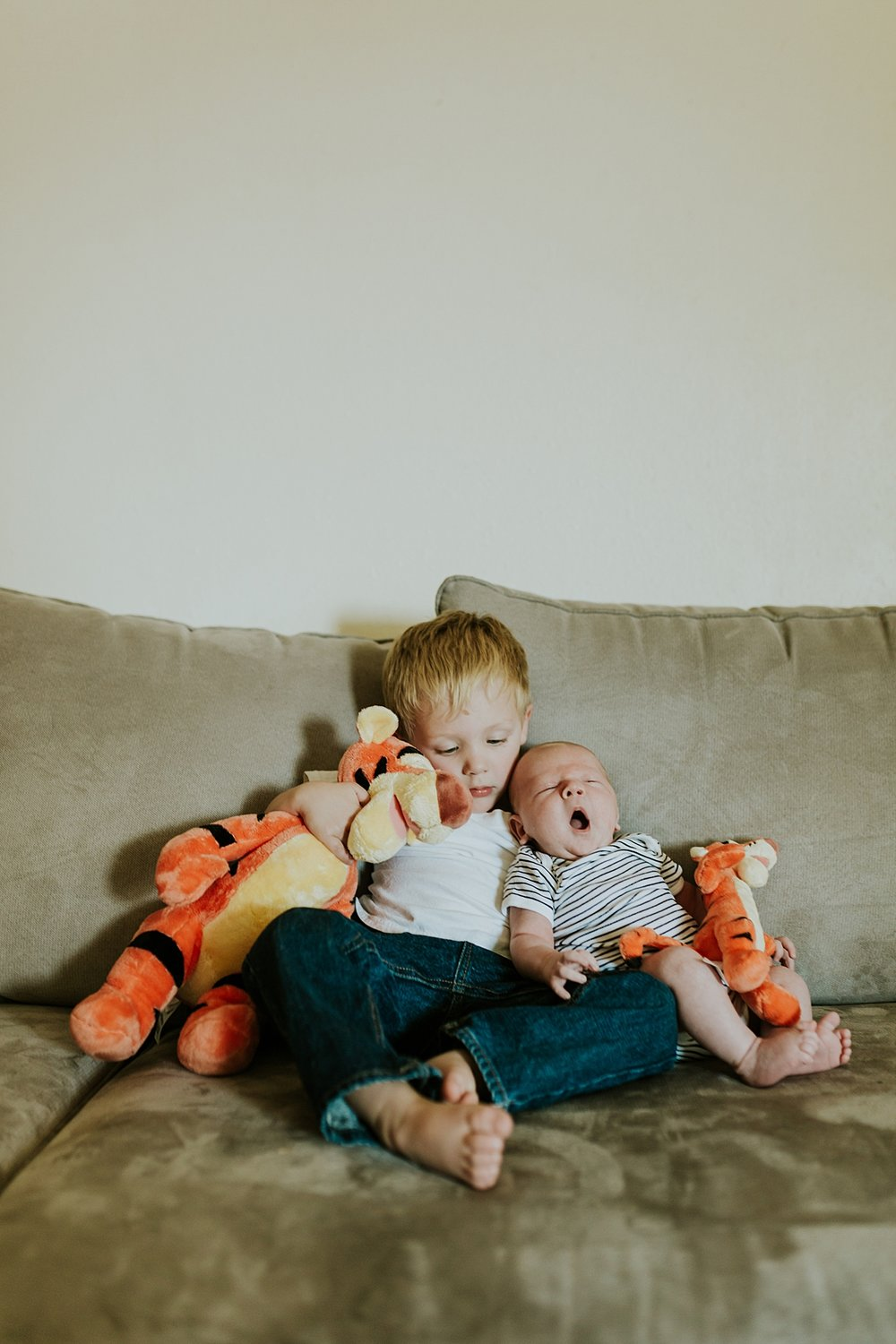 Orange County family photographer. Photo of brothers with their stuffed toys as they sit on the couch during in home newborn session with Krystil McDowall Photography