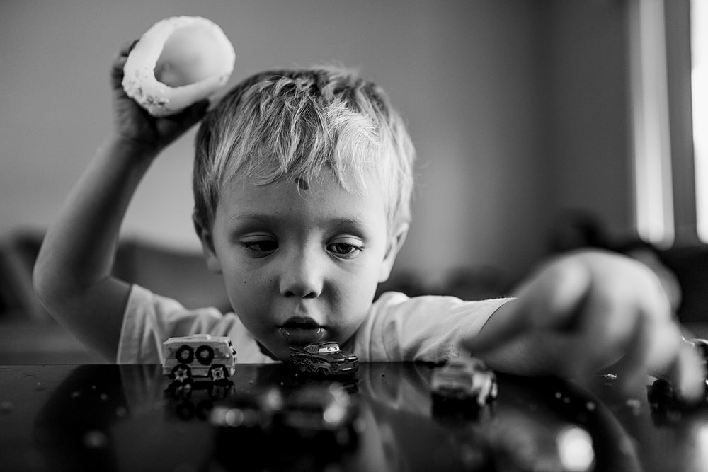 Orange County family photographer. Black and white photo of young boy playing with cars in his living room during in home newborn session with Krystil McDowall Photography