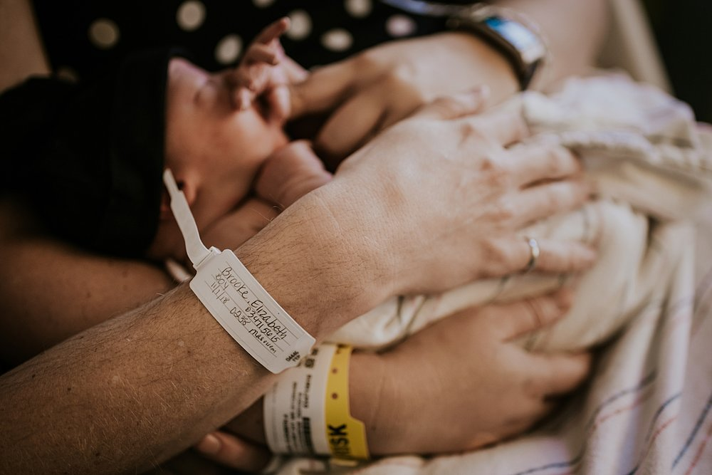 Orange County family photographer. Photo of mom and dad's hospital wrist bands as they hold their two day old newborn baby during fresh 48 session with Krystil McDowall Photography