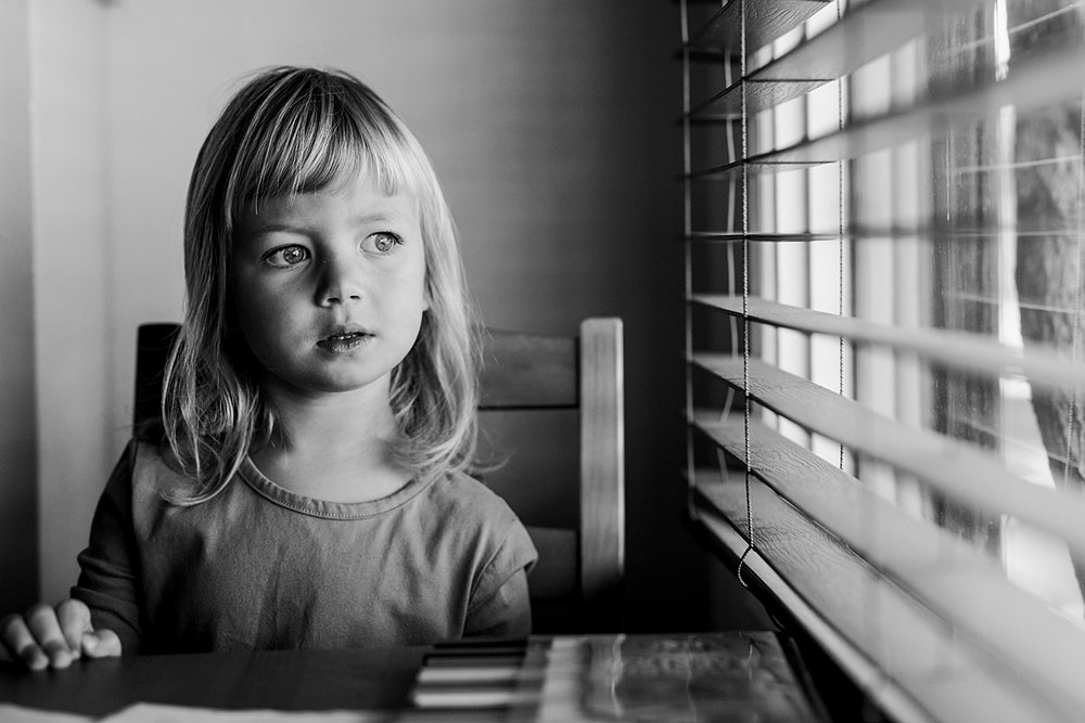 Orange County family photographer. Black and white portrait of beautiful four year old girl in mustard dress and big blue eyes taken during in home family session in Long Beach